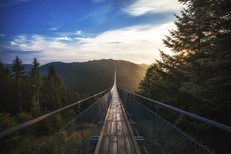 Empty suspension footbridge over mountains against sky
