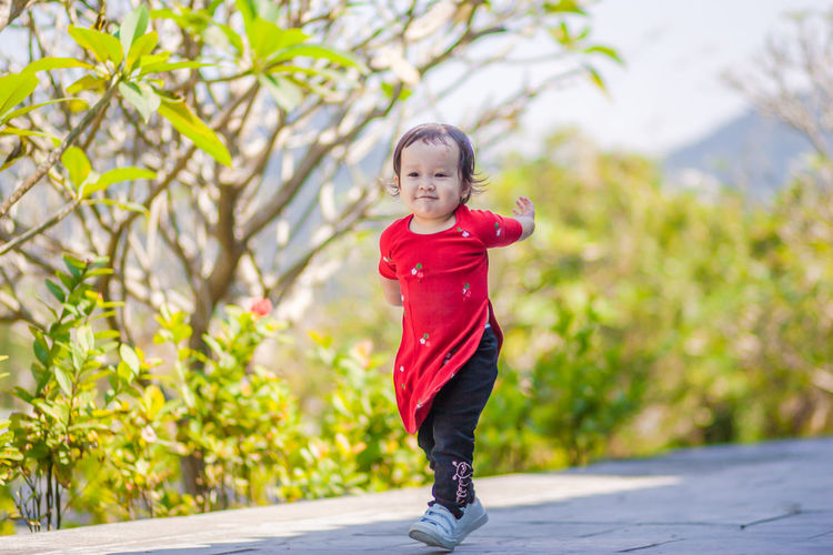 """Tet"" holiday of Vietnam (aka Lunar New Year) Daughter Kid Running Lunar New Year Tet Holiday Happy Vietnamese Traditional Dress Ao Dai Adorable Morning Temple Tree Blond Hair Portrait Full Length Child Childhood Smiling Healthy Lifestyle Happiness Looking At Camera"