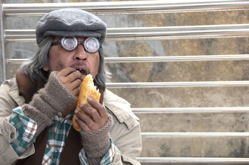 Homeless man on street and eating old bread. Adult Architecture Casual Clothing Clothing Day Eating Fast Food Food Food And Drink Freshness Front View Holding Hungry Leisure Activity Lifestyles One Person Portrait Real People Snack Take Out Food Unhealthy Eating Warm Clothing Winter