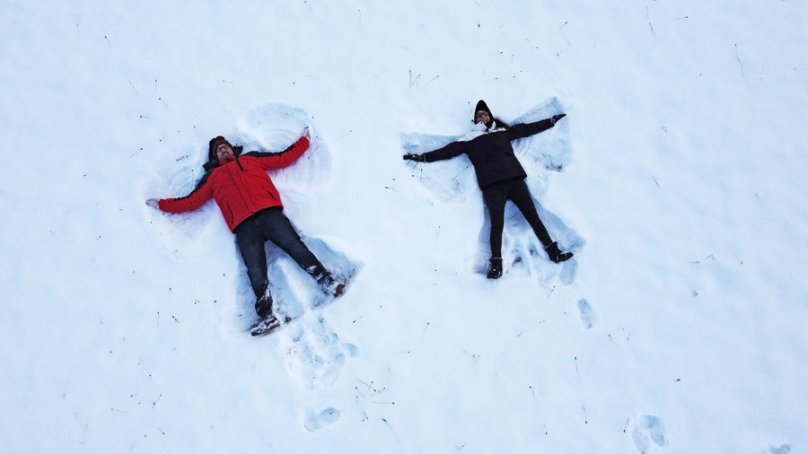 Aerial view of couple lying on snow covered land during winter
