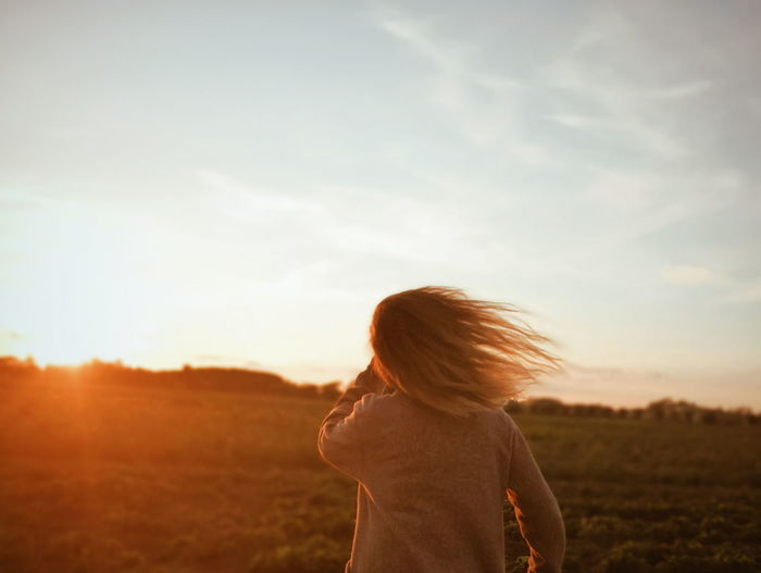 Rear View Of Girl Standing On Field During Sunset