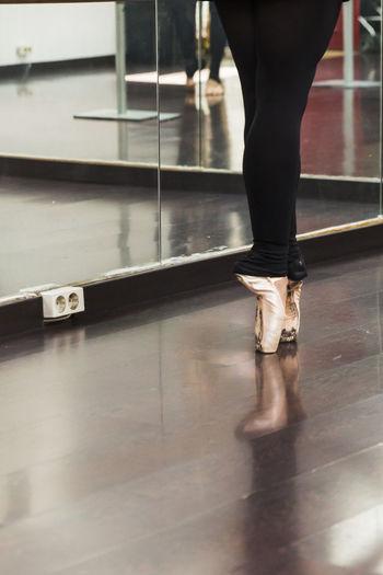 Low section of ballet dancer practicing on floor