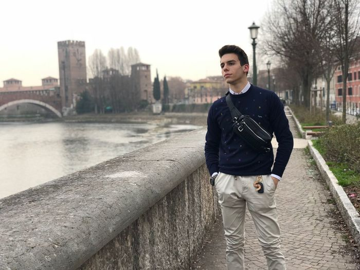 Italy Verona Bridge Influencer Outfit Verona Architecture Young Adult One Person Built Structure City Young Men Building Exterior Clothing Casual Clothing Men Standing Leisure Activity Looking Away Adult Contemplation My Best Travel Photo