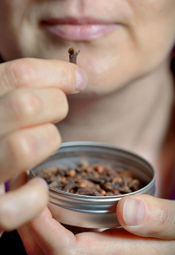 Close-up midsection of mature woman holding cloves in container