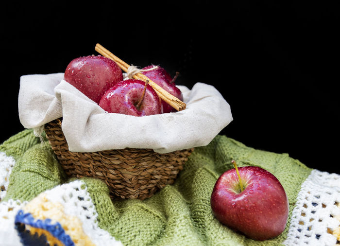Healthy and organic red apples in a wicker basket and a stick cinnamon on black background with copy space Indoors  Studio Shot Fruit Healthy Eating Close-up Textile Freshness Wool Selective Focus Apple Red Organic Healthy Wicker Basket Cinnamon Copy Space Background Wallpaper Fresh No People Rustic Summer Diet Tasty Delicious Nutrition Agriculture Drops Water
