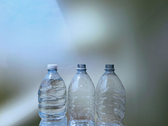 Close-Up Of Bottles Against Gray Background