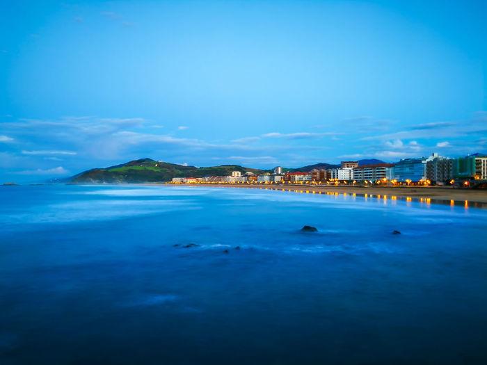 Illuminated buildings by sea against blue sky