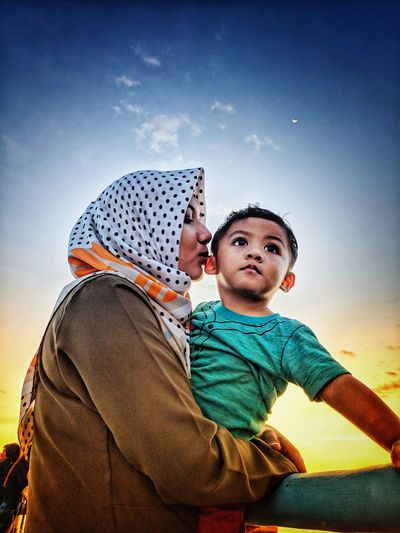 Mother kissing son against sky during sunset