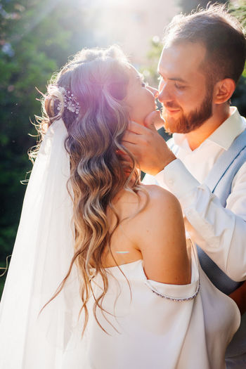 Newlywed couple embracing while standing outdoors