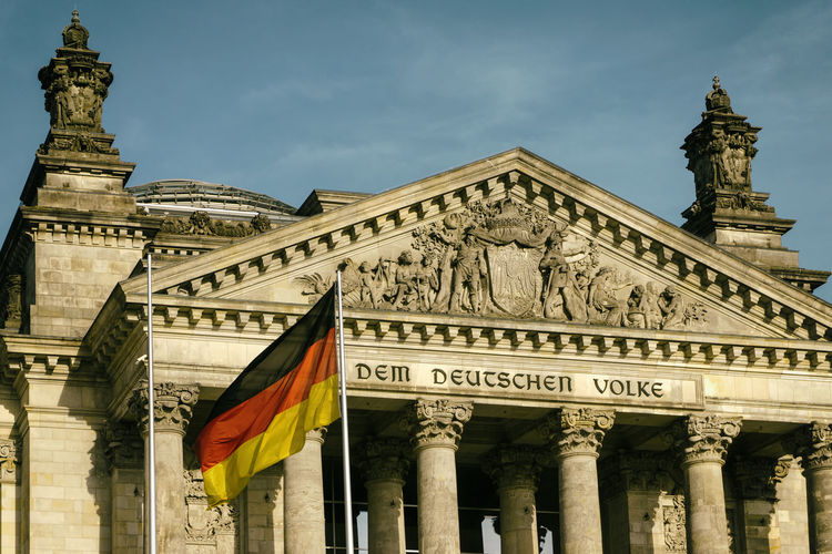 Entrance to Reichstag building with national flag Architecture Berlin Germany 🇩🇪 Deutschland Horizontal Reichstag Building Architectural Column Architecture Building Exterior Built Structure City Color Image Day Flag Government History Low Angle View No People Outdoors Patriotism Sculpture Sky Statue Sun Travel Destinations