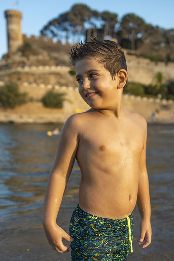 Shirtless boy standing by water outdoors