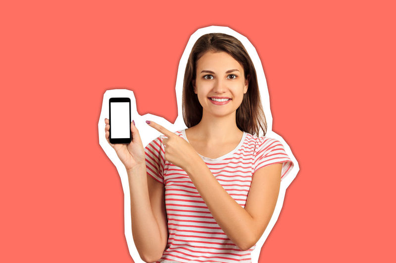 Portrait of smiling young woman using phone against orange background