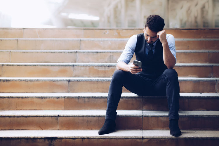 Full length of young man sitting on staircase
