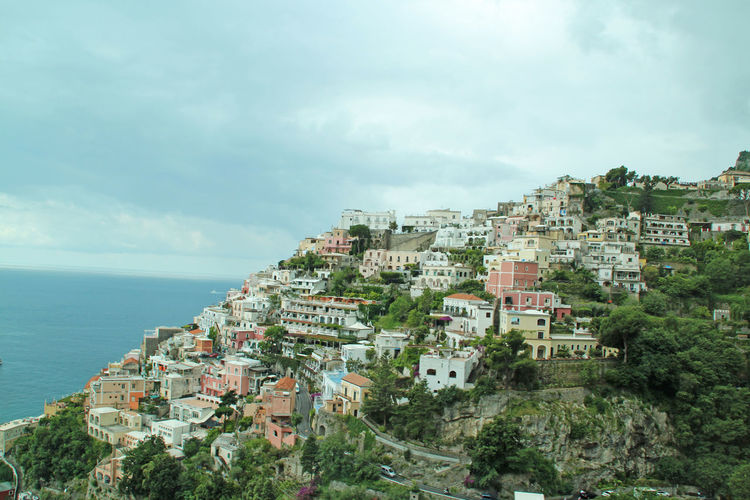 Positano On Mountain By Tyrrhenian Sea Against Cloudy Sky
