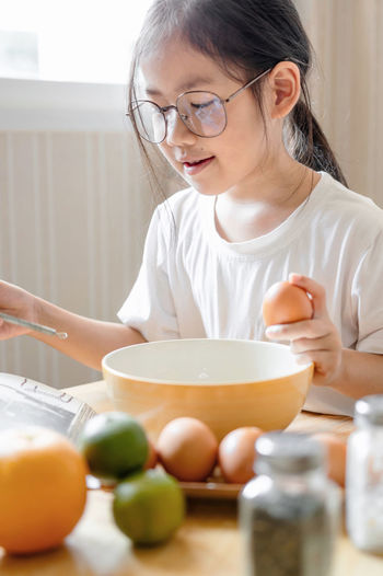 Girl reading book while preparing food at home