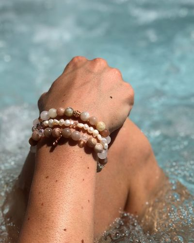 Cropped image of woman wearing bracelet in swimming pool