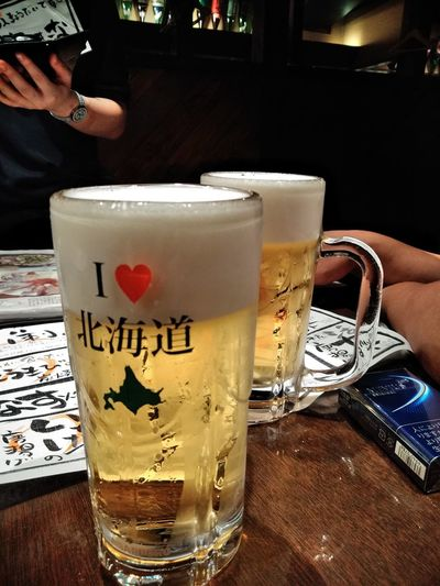 Close-up of hand holding beer glass on table