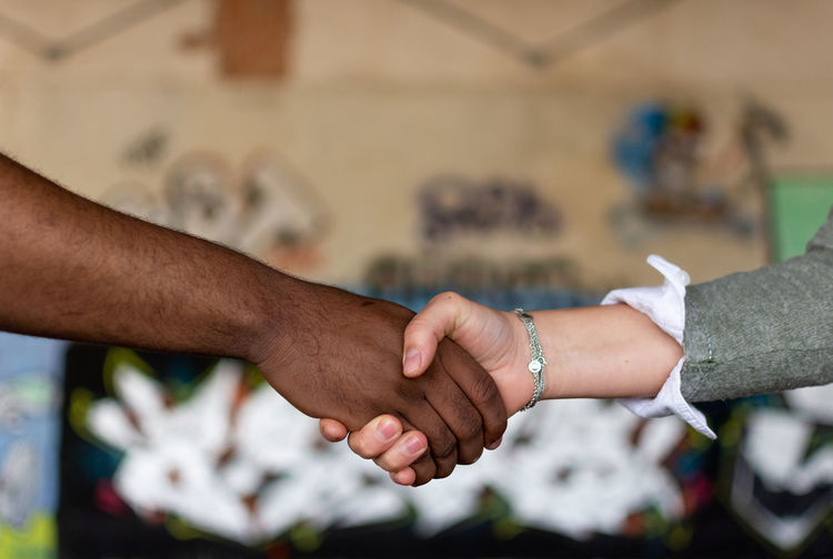 Cropped image of people shaking hands outdoors