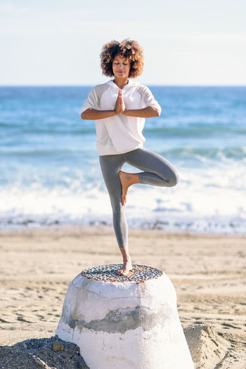 Young black woman doing yoga in the beach. Female wearing white sport clothes in tree asana with defocused sea background. Afro hairsytle. Balance Beach Beautiful Woman Beauty In Nature Day Exercising Flexibility Focus On Foreground Full Length Horizon Over Water Leisure Activity Lifestyles Nature One Person Outdoors Real People Sand Scenics Sea Standing Water Women Yoga Young Adult Young Women