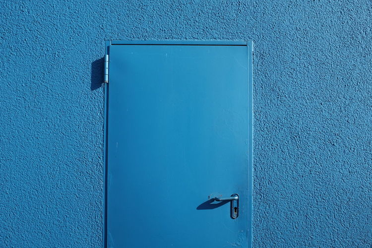 Closed blue door on wall