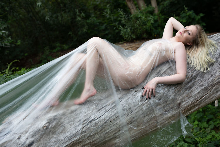 Portrait of naked woman wrapped in a polythene lying won on tree trunk in forest