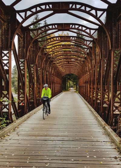 A man in a fluorescent yellow jacket riding a bicycle on a bridge.