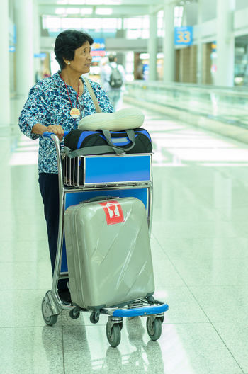 Senior Woman With Luggage In Cart Standing At Airport