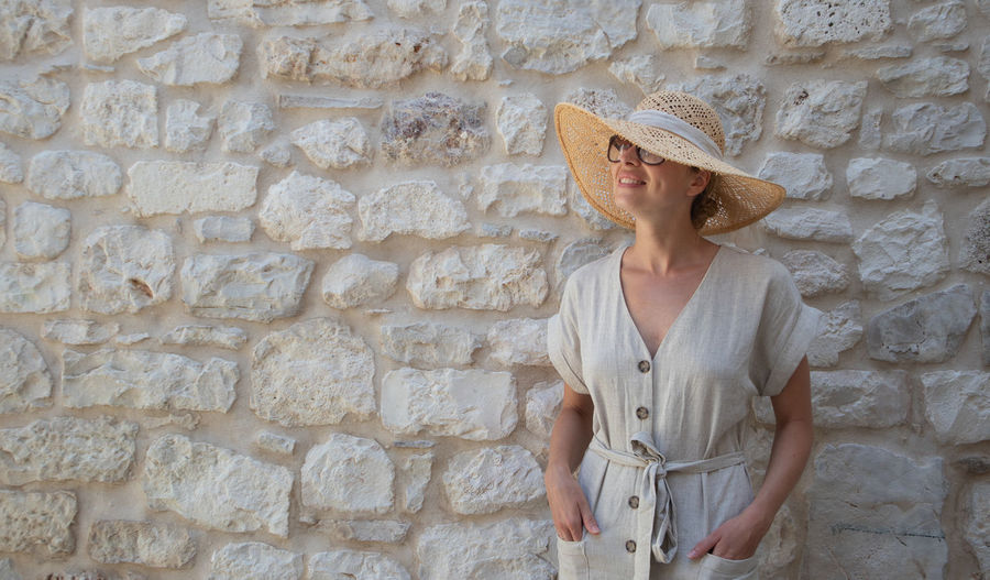 Midsection of woman wearing hat against wall
