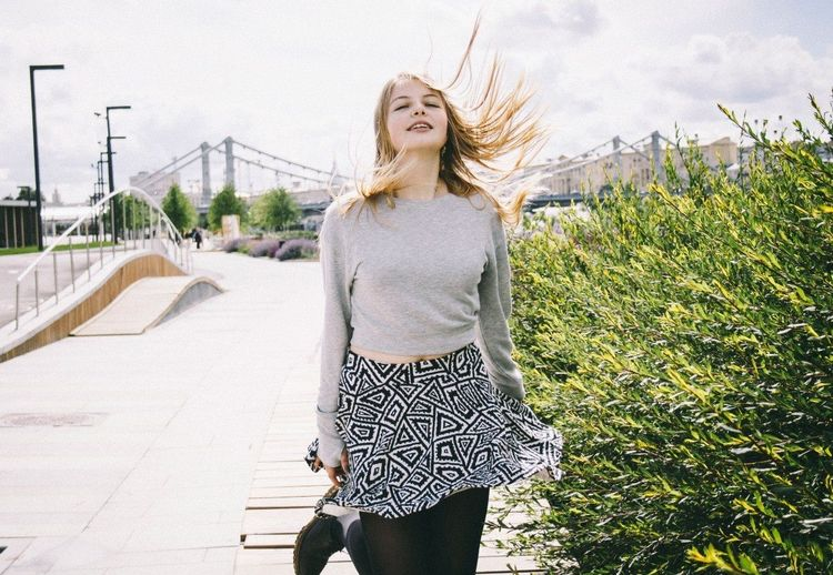 Portrait of a young woman with windy blonde hair on road