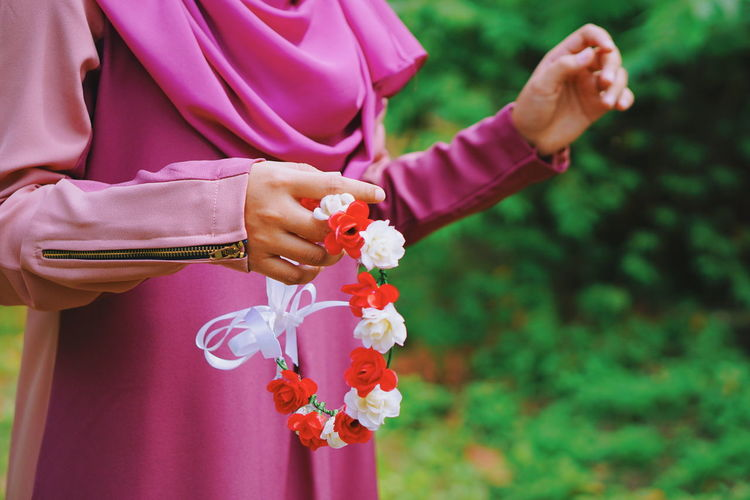 Midsection Of Woman Holding Floral Headband