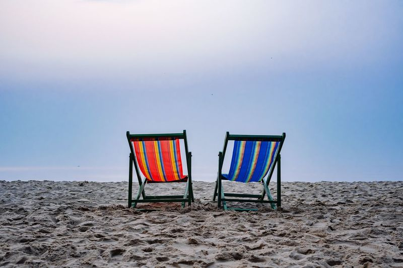 Chairs on beach against sky