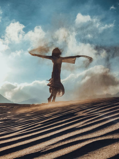Low angle view of woman with arms outstretched against sky