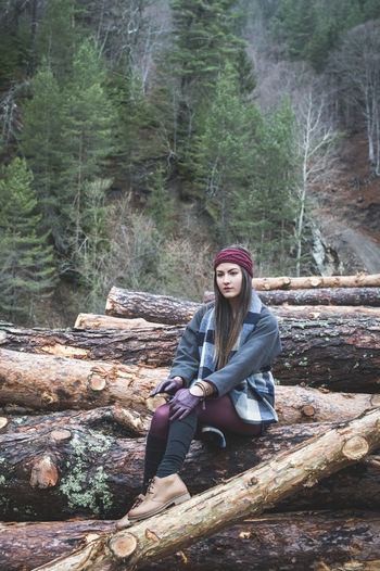 Young woman sitting on logs of wood in forest