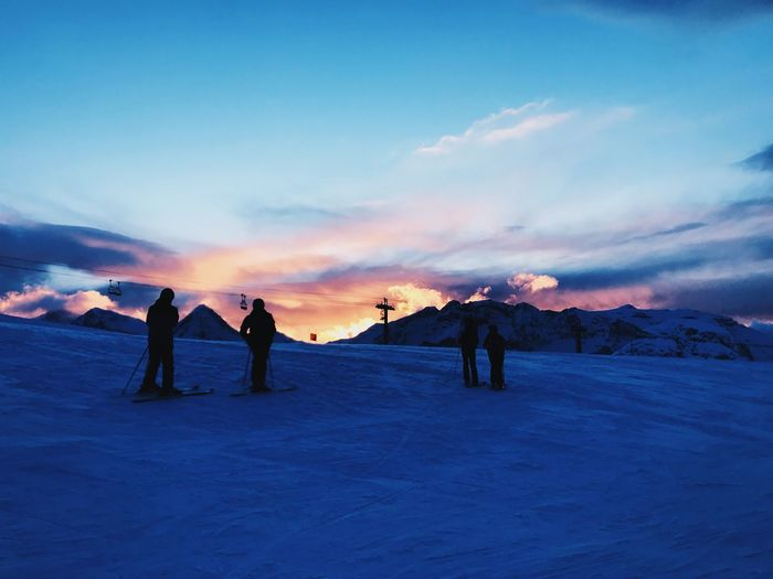 Silhouette People Skiing On Snowcapped Mountain Against Sky During Sunset