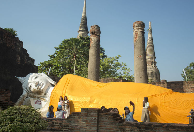 Tourist visiting buddhist temple against blue sky