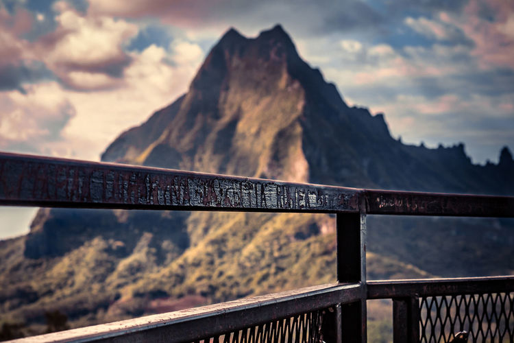 Close-up of text on railing against mountain