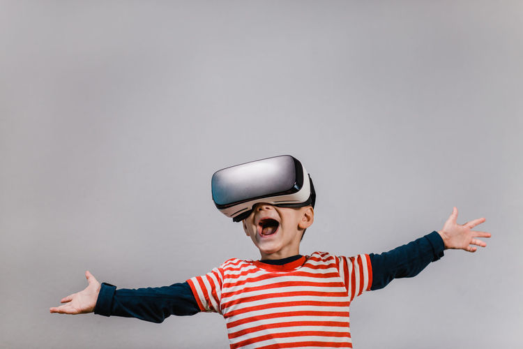Excited kid with hands spread having fun with VR glasses. Portrait of happy child wearing virtual reality headset against grey background. Child Front View Striped Mouth Open One Person Indoors  Vr Virtual Reality Portrait Boy Red Color Headset Glasses Caucasian Technology Preschool Isolated Gadget Digital E-learning 3D Horizontal Education Hands Spread Having Fun