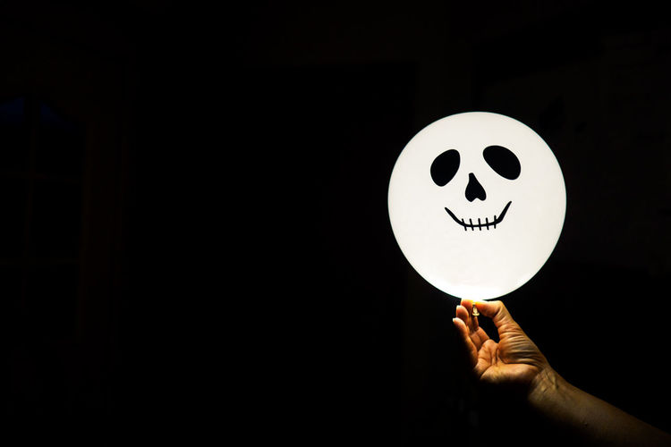 Cropped Hand Holding Balloon With Anthropomorphic Face Over Black Background