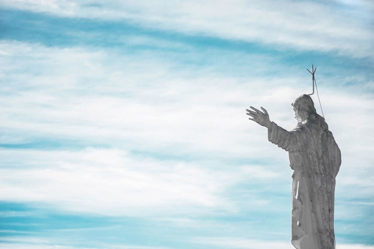 Low angle view of jesus christ statue against cloudy sky