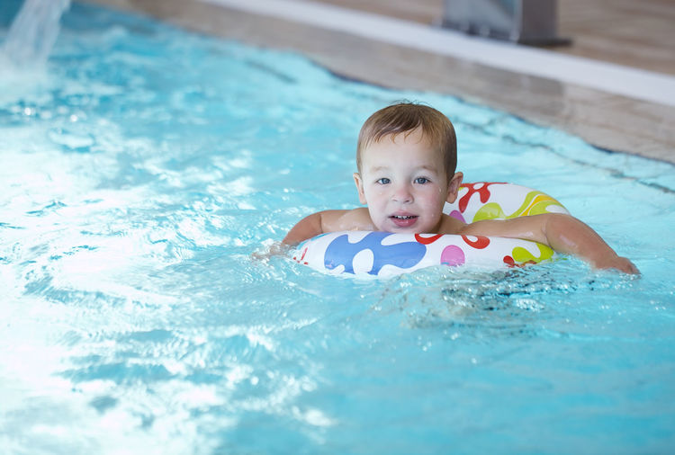Portrait of boy with inflatable ring in swimming pool
