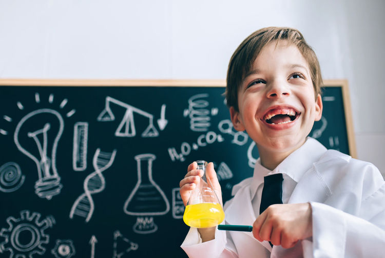 Boy Wearing Lap Coat While Standing In Classroom