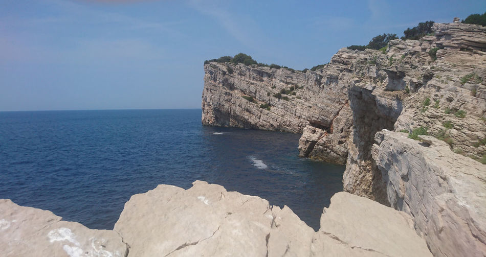 Scenic view of sea by cliff against clear sky