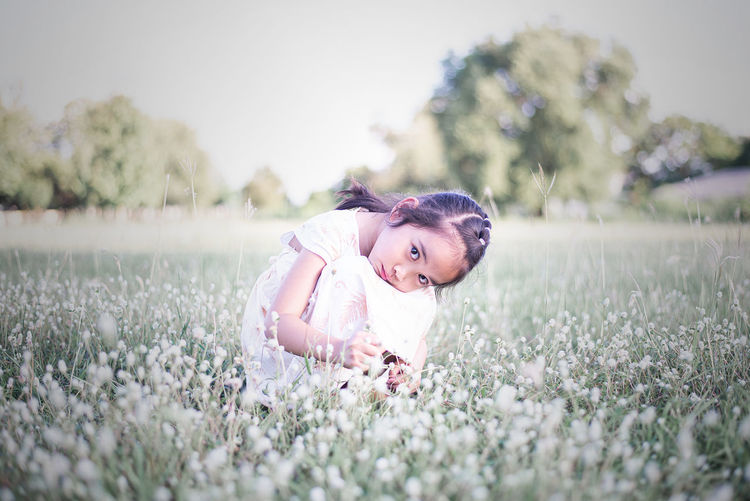 Portrait of girl with flowers on field
