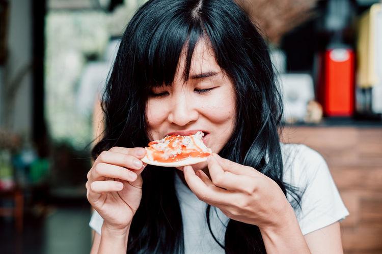 Asian woman eating homemade pizza at restaurant.