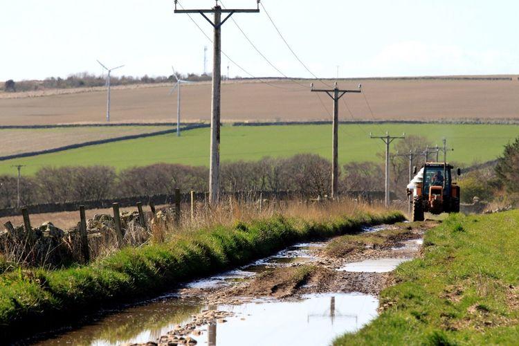 Tractor on dirt road amidst farm field