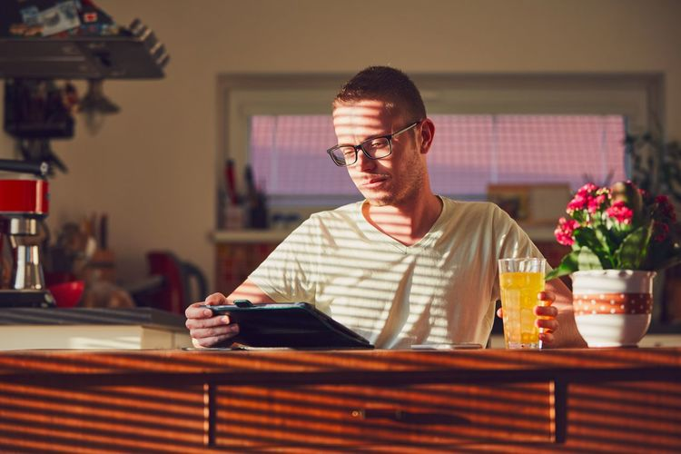 Young man using digital tablet while sitting at home