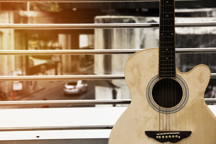 Close-Up Of Guitar Against Railing On Balcony
