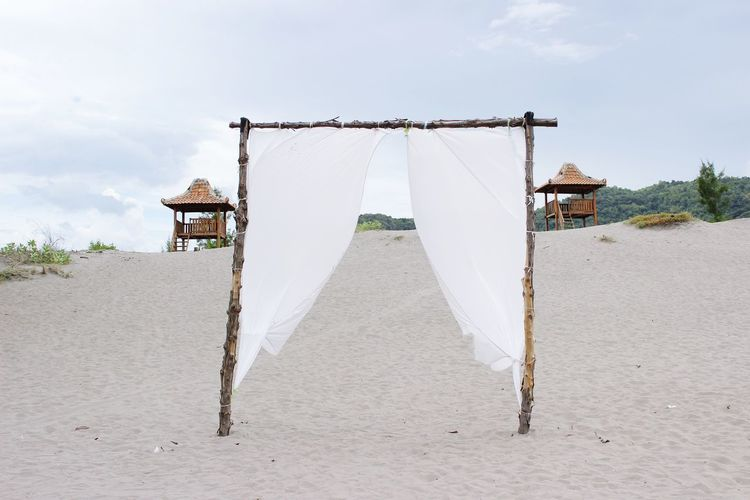 Clothes drying on beach by building against sky