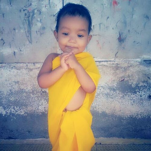 Child Children Only Childhood Yellow One Person Girls Standing Outdoors Lifestyles People Religion Front View Day Looking Down Hands Clasped Hand On Chin Cute Wall Clothing
