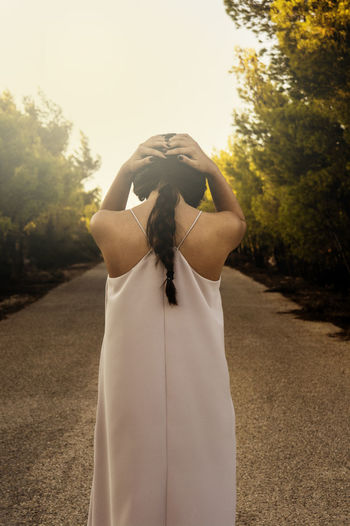 Rear View Of A Woman With Hands Behind Head